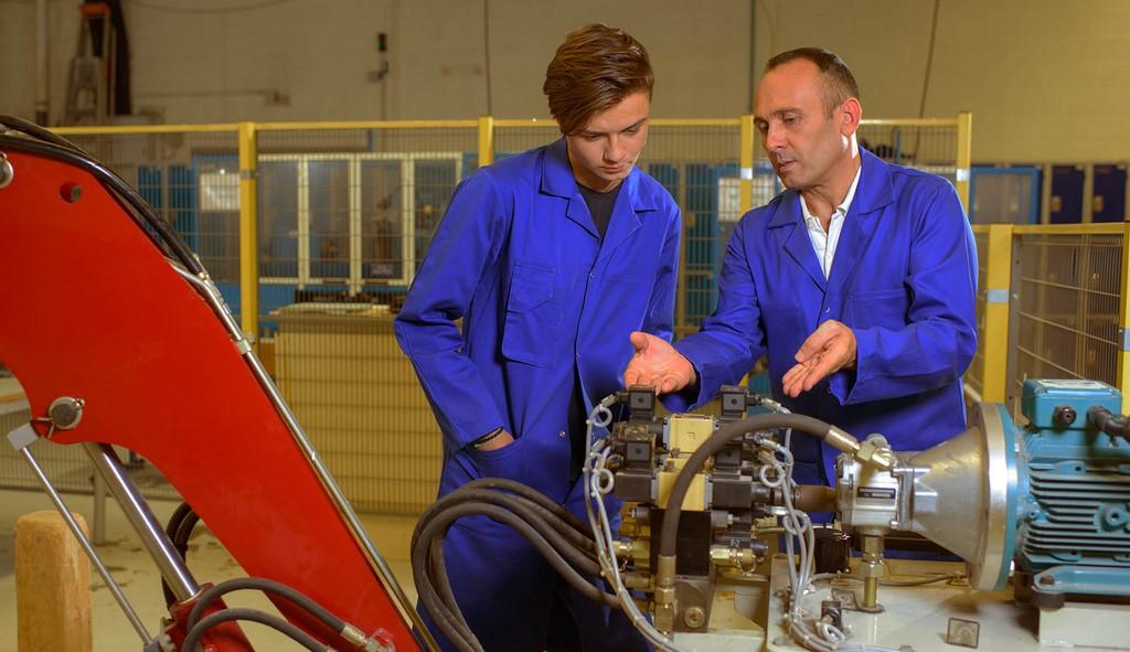 Engineers looking at hydraulic arm mechanicsm